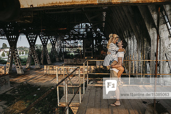 Happy young man carrying girlfriend in an old train station