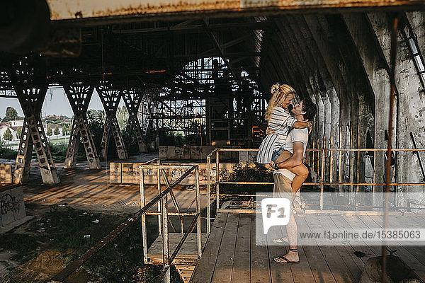 Glücklicher junger Mann mit Freundin in einem alten Bahnhof