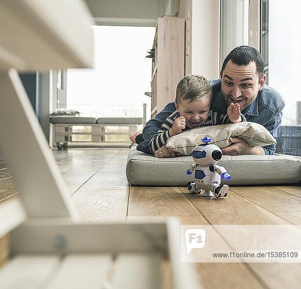 Aufgeregter Vater und Sohn liegen zu Hause auf einer Matratze und schauen einem Spielzeugroboter zu