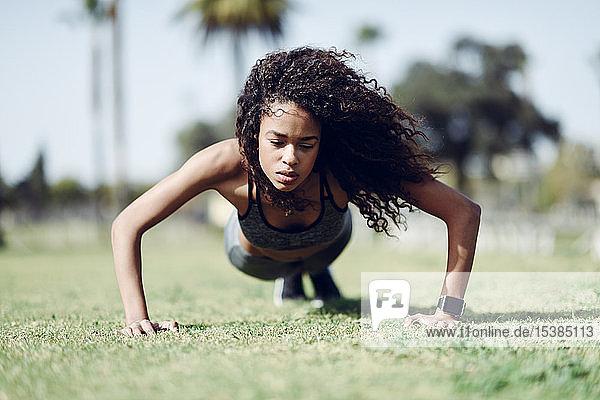 Sportliche junge Frau macht Liegestütze auf dem Rasen
