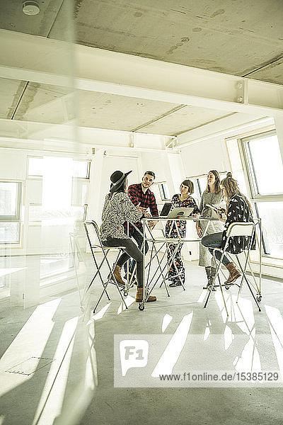 Gruppe von kreativen Fachleuten trifft sich in einem hellen Büro und diskutiert neue Lösungen