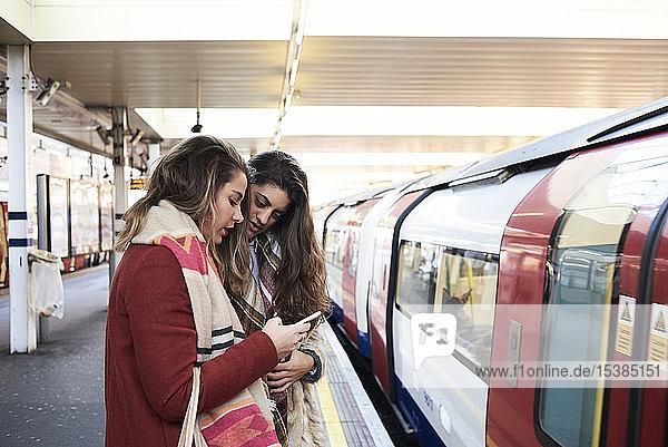 UK  London  two women using cell phone at underground station platform
