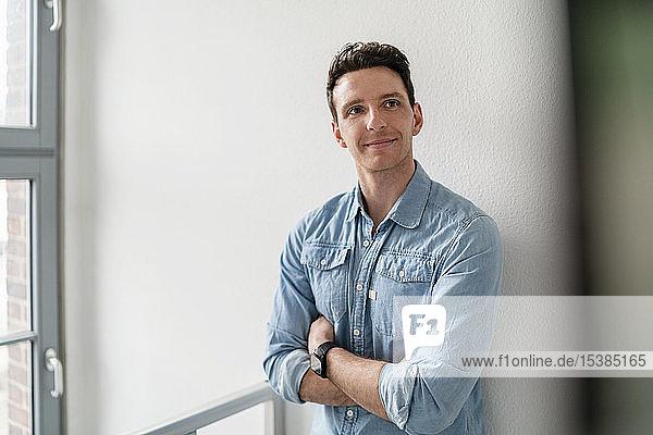 Porträt eines selbstbewussten Geschäftsmannes am Fenster im Amt