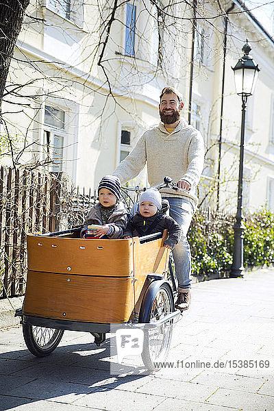 Glücklicher Vater mit zwei Kindern auf dem Lastenfahrrad in der Stadt
