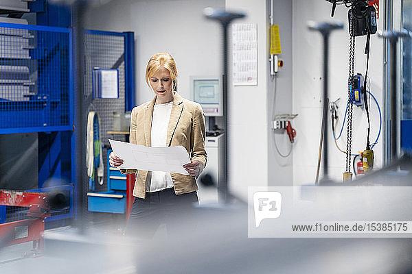 Geschäftsfrau betrachtet Plan in Fabrik