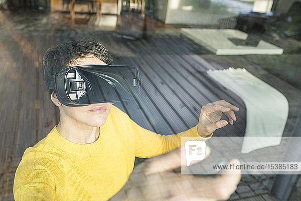 Portrait einer Frau hinter einer Fensterscheibe mit Virtual-Reality-Brille zu Hause