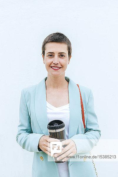Frau in Anzugjacke mit Thermobecher vor weißer Wand