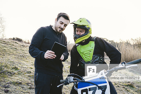 Motocross im Gespräch mit dem Trainer mit Tablet Motocross im Gespräch mit dem Trainer mit Tablet