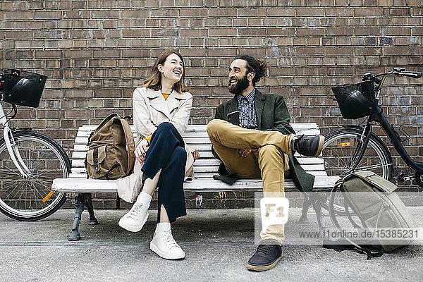 Glückliches Paar sitzt auf einer Bank neben E-Bikes und unterhält sich