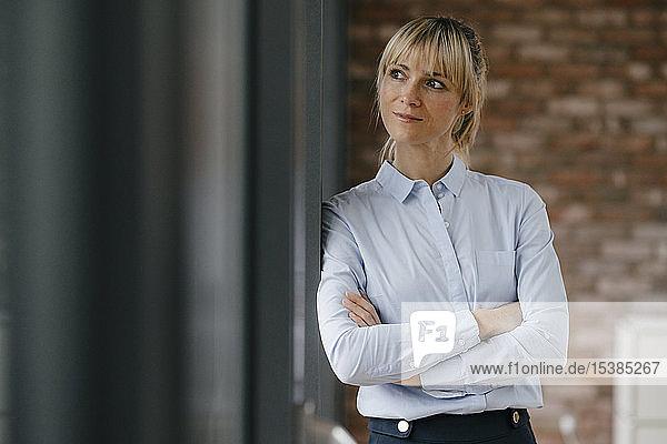 Porträt einer blonden Geschäftsfrau mit verschränkten Armen