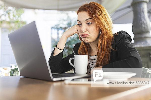 Porträt einer rothaarigen jungen Frau im Straßencafé  die auf ihren Laptop schaut