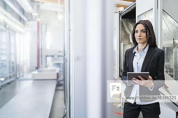 Businesswoman using tablet in a modern factory