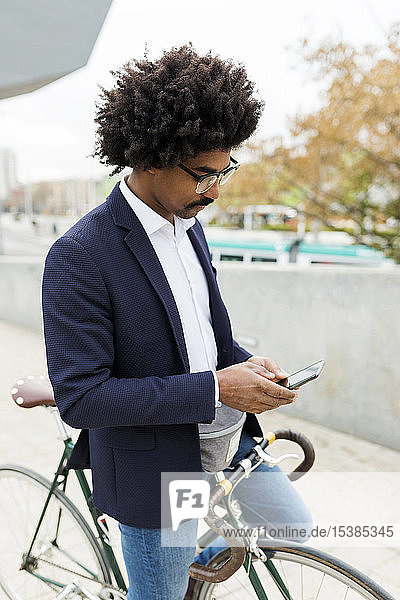 Spain  Barcelona  businessman on bicycle using cell phone in the city