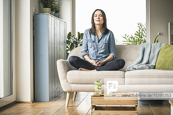 Woman sitting on the couch at home with closed eyes