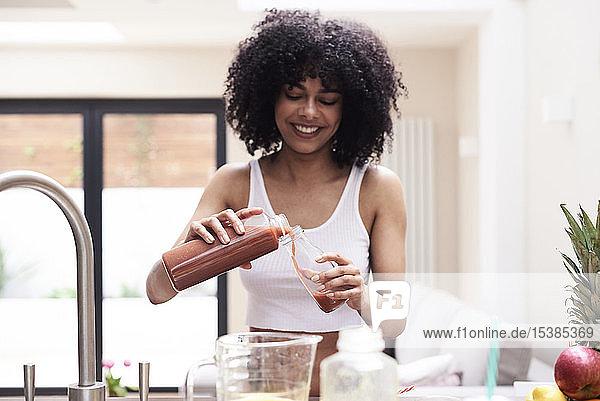Lächelnde junge Frau bereitet gesunden Smoothie in der Küche