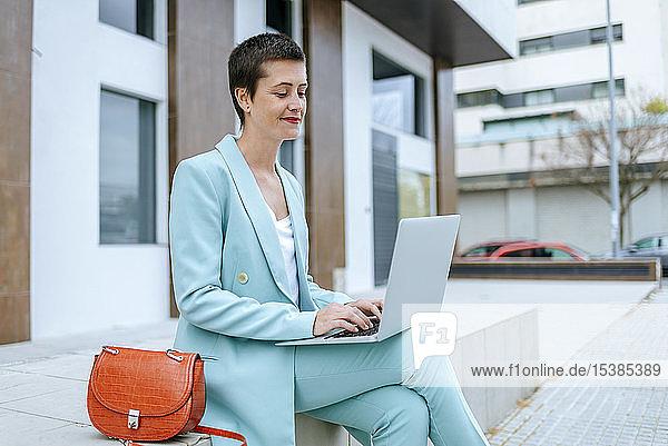 Frau in Anzugsjacke benutzt Laptop im Freien