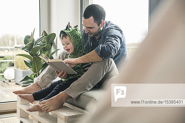Boy in a costume with father reading book at home