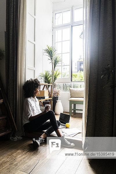 Entspannte Frau sitzt auf dem Boden ihrer Wohnung und trinkt Kaffee