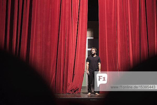 Barfüssiger Schauspieler auf Theaterbühne stehend Barfüssiger Schauspieler auf Theaterbühne stehend