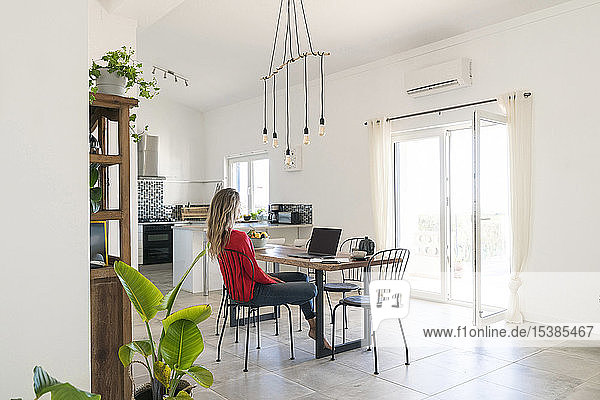 Woman using laptop on dining table in modern home