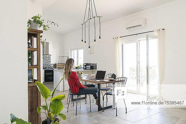 Frau benutzt Laptop auf dem Esstisch im modernen Haus
