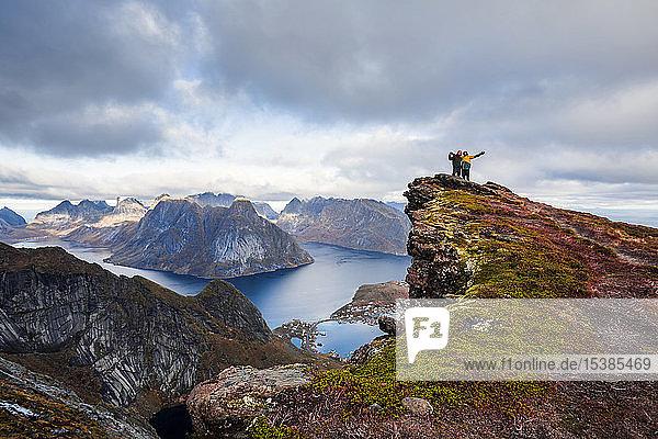 Norway  Lofoten Islands  Reine  men with raised arms standing on Reinebringen