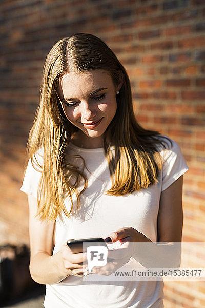Junge Frau vor Backsteinmauer  mit Smartphone