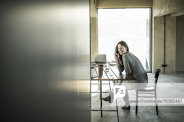 Frau sitzt im Büro und benutzt ein Smartphone