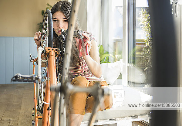 Young woman reparing bicycle at home