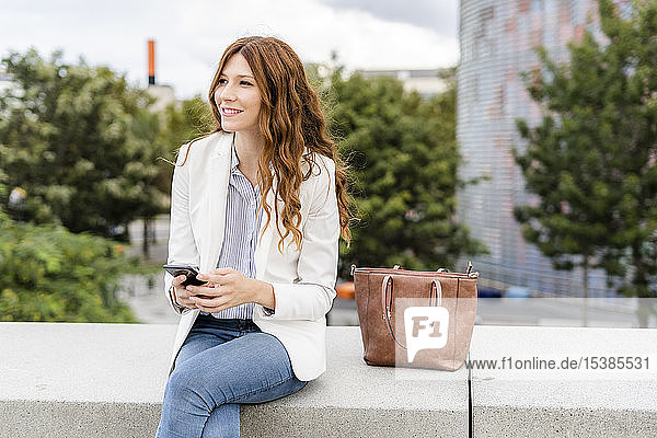 Young businesswoman commuting in the city  using smartphone  sitting on a wall