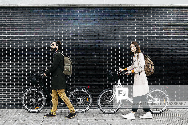 Ehepaar schiebt E-Bikes an einer Ziegelmauer entlang