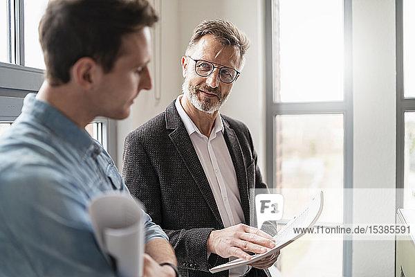 Zwei Kollegen im Gespräch am Fenster im Büro