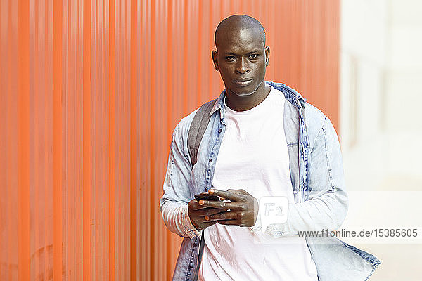 Portrait of man with smartphone wearing casual denim shirt