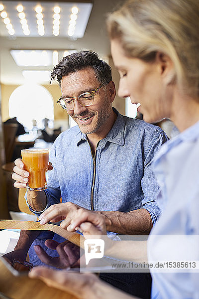Smiling woman and man using tablet in a cafe