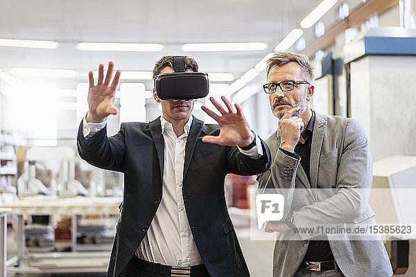 Zwei Geschäftsleute mit VR-Brillen in der Fabrik