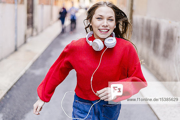 Young woman wearing red pullover  running