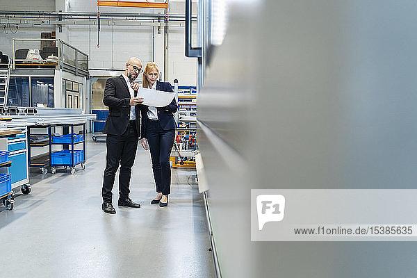 Geschäftsmann und Geschäftsfrau betrachten Plan in Fabrik