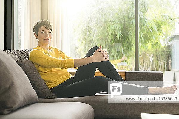Porträt einer lächelnden Frau  die sich zu Hause auf der Couch entspannt