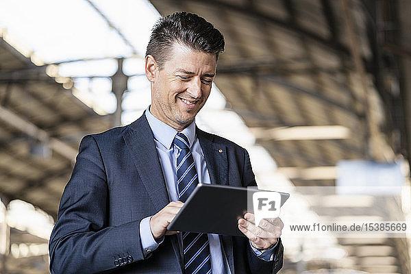 Lächelnder Geschäftsmann mit Tablette am Bahnhof