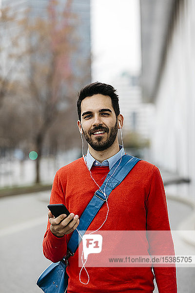 Casual businessman commuiting in the city  using earphones and smartphone