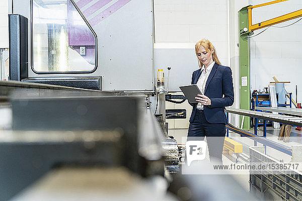 Geschäftsfrau mit Tablette in einer Fabrik