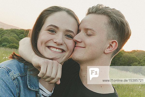 Porträt einer glücklichen Teenagerin mit Freund in der Natur am Abend