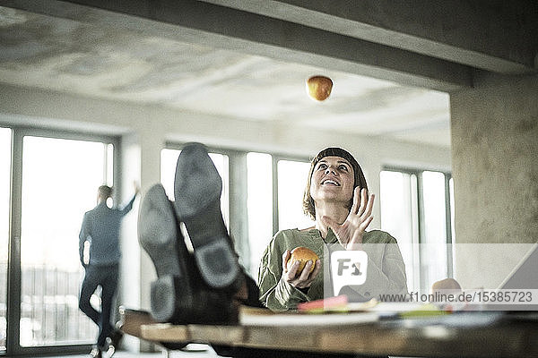 Woman juggling apples in the office  sitting with feet on desk