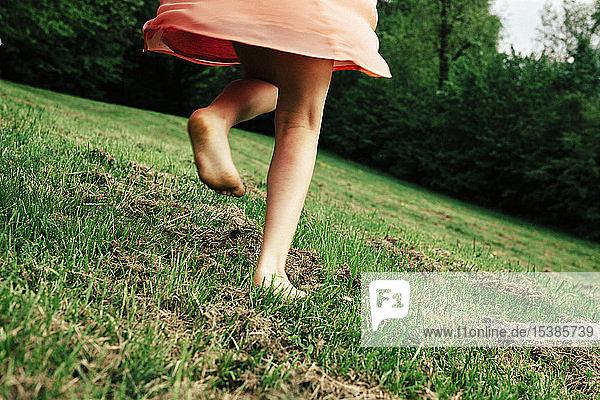 Rückenansicht eines barfuss auf einer Wiese laufenden Mädchens  Teilansicht