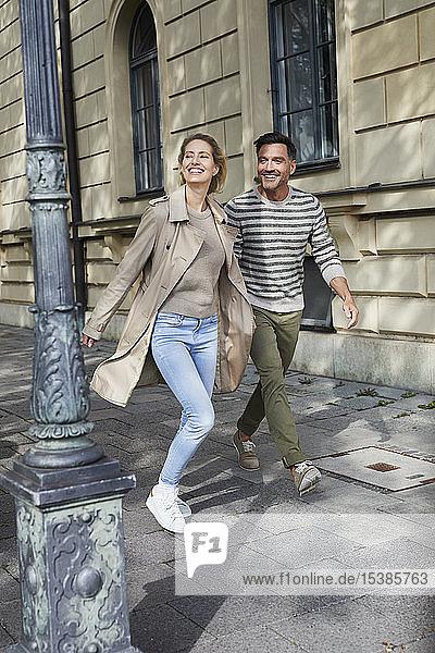 Glückliches Paar beim Spaziergang auf dem Bürgersteig in der Stadt