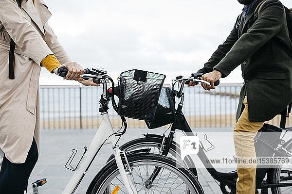 Nahaufnahme eines Paares mit E-Bikes an der Strandpromenade