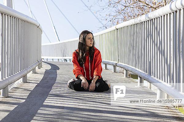 Junge zeitgenössische Tänzerin auf einer Fußgängerbrücke sitzend