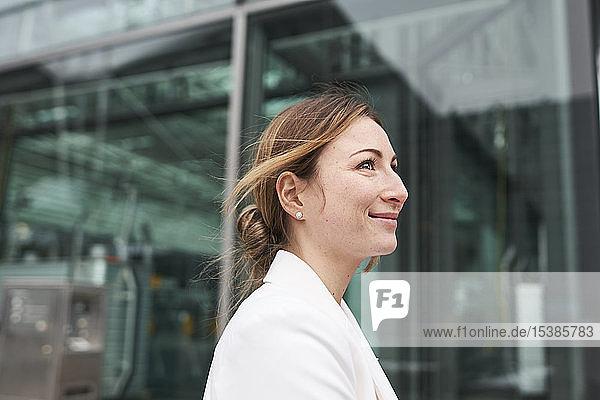 Porträt einer lächelnden jungen Geschäftsfrau vor einem Gebäude