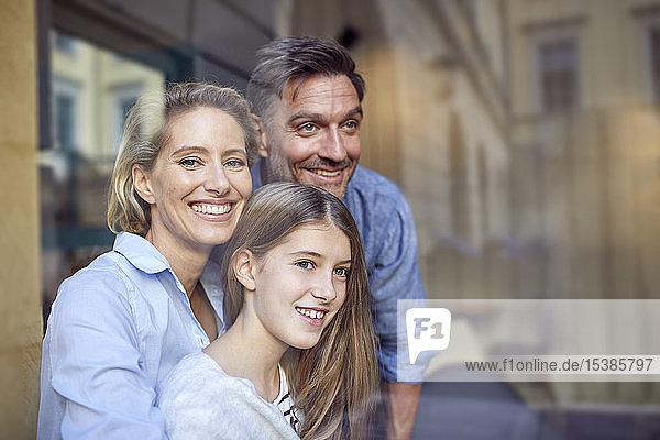 Porträt einer glücklichen Familie hinter einer Fensterscheibe