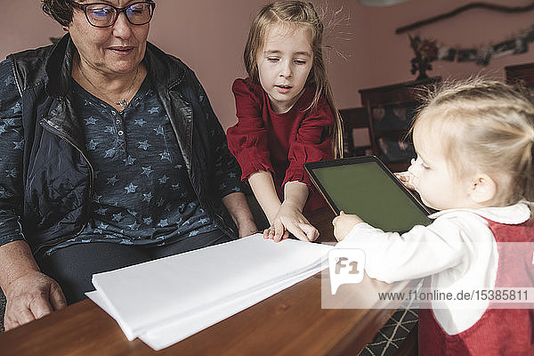 Zwei Mädchen und ihre Großmutter spielen im Wohnzimmer mit Papier und Tablette